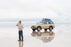 Man och bil på sjön Salar de Uyuni Royaltyfri Bild