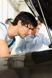 Man- och bilmekaniker som ser under en huv Royaltyfria Foton