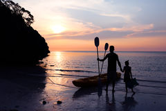 Man och dotter som kayaking på stranden Royaltyfria Bilder