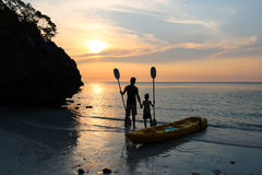 Man och dotter som kayaking på stranden Royaltyfri Bild