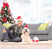 Man och en hund med jultomtenhattar som hemma sitter Royaltyfria Foton