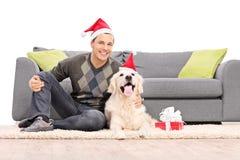 Man och en hund med jultomtenhattar som sitter vid en soffa Arkivbilder