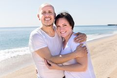 Man och ett medelålderst kvinnasammanträde på stranden arkivfoton