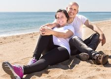 Man och ett medelålderst kvinnasammanträde på stranden arkivfoto
