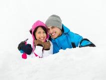 Man och flicka som ligger i snö Arkivbild