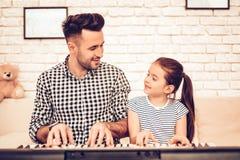 Man- och flickalekpiano Lekpiano tillsammans FaderAnd Daughter On soffa Spendera tid tillsammans dagfader s Manlek med flickan arkivbild