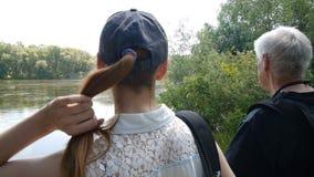 Man- och flickavandring tillsammans Fotvandrare med ryggs?ckar De stoppar på flodbanken och ser ut på den Flicka som trycker p? o stock video