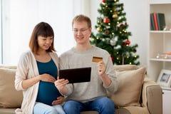 Man och gravid fru som direktanslutet shoppar på jul Arkivbild