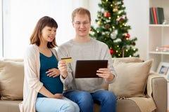 Man och gravid fru som direktanslutet shoppar på jul Arkivfoto