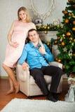 Man och gravid kvinna som står det near julträdet arkivfoto