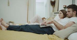 Man och hans flickvän i morgonen, i säng, hemtrevlig design, läsebok och att se på bärbara datorn arkivfilmer