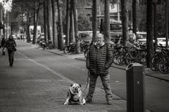 Man och hans hund, gataståenden, liknande ställing Royaltyfri Fotografi