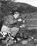 Man och hans hund som campar och förbereder mat (alla visade personer inte är längre uppehälle, och inget gods finns Leverantörga Arkivbild