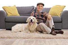Man och hans hund tillsammans på golvet Arkivbilder