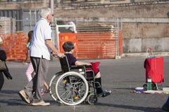 Man och henne rörelsehindrad fru i rullstolen Arkivbild