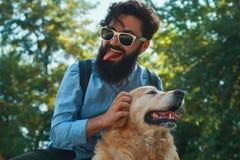 Man och hund som har gyckel, spela som gör roliga framsidor medan restin royaltyfria foton