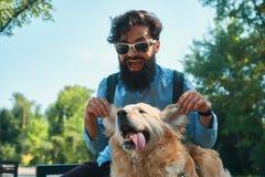 Man och hund som har gyckel, spela som gör roliga framsidor medan restin fotografering för bildbyråer