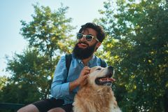 Man och hund som har gyckel, spela som gör roliga framsidor medan restin royaltyfria bilder