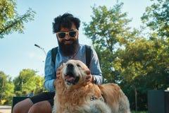 Man och hund som har gyckel, spela som gör roliga framsidor medan restin royaltyfri foto