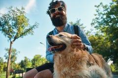 Man och hund som har gyckel, spela som gör roliga framsidor medan restin royaltyfri fotografi