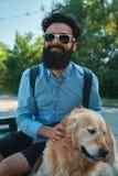 Man och hund som har gyckel, spela som gör roliga framsidor medan restin arkivfoton