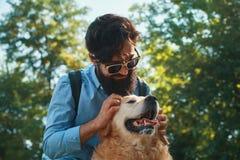 Man och hund som har gyckel, spela som gör roliga framsidor medan restin arkivbild