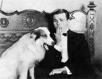 Man och hund som sitter tillsammans att gäspa (alla visade personer inte är längre uppehälle, och inget gods finns Leverantörgara Royaltyfri Bild