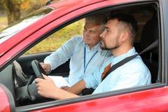 Man och instruktör i bil arkivfoto