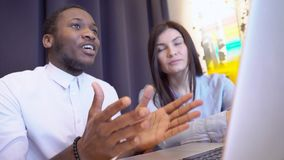 Man och kvinna för mång- etniska par som ung talar, genom att använda bärbara datorn i modernt kontor lager videofilmer