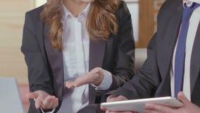 Man och kvinna i affärsdräkten som har diskussion över data från bärbara datorn, karriär arkivfilmer