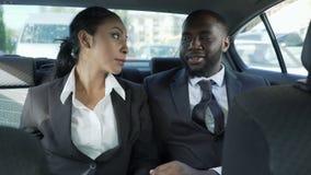 Man och kvinna i affärsdräkter som sitter på baksätet av bilen som flörtar, affektion stock video