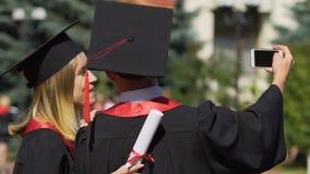Man och kvinna i akademiska kappor och lock som tar selfie på avläggande av examenceremoni lager videofilmer