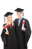 Man och kvinna i avläggande av examenkappor som rymmer diplom Royaltyfria Foton