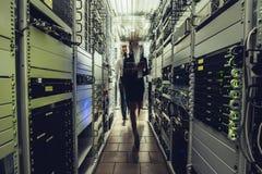 Man och kvinna i datacenter royaltyfria foton