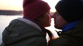 Man och kvinna i hattar som kysser på solnedgången vid floden slowmotion HD, 1920x1080 stock video