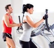 Man och kvinna med den ellipsformiga korsinstruktören på idrottshallen Arkivfoto