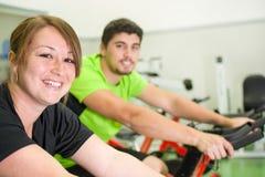 Man och kvinna med den stationära cykeln i idrottshall royaltyfria bilder