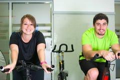 Man och kvinna med den stationära cykeln i idrottshall royaltyfria foton