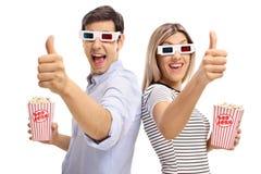 Man och kvinna med exponeringsglas 3D och hållande tummar för popcorn upp Royaltyfri Bild