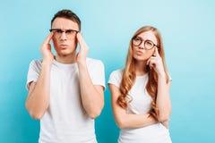 Man och kvinna med exponeringsglas som fokuseras och som är eftertänksamma, på ett ljust - blå bakgrund royaltyfria bilder