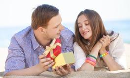 Man och kvinna med gåvan på en strand. Arkivfoto