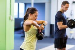 Man och kvinna med kettlebell som övar i idrottshall Royaltyfri Bild