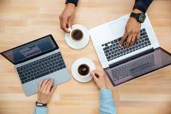 Man och kvinna med två bärbara datorer som tillsammans dricker kaffe arkivfoton