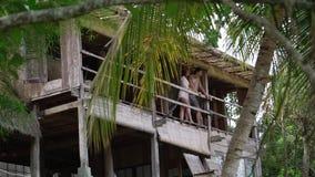 Man och kvinna på terrass i djungelvilla på den soliga dagen lager videofilmer