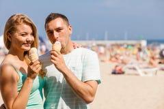 Man och kvinna som äter glass på stranden Royaltyfri Fotografi