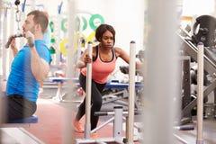Man och kvinna som övar genom att använda utrustning på en upptagen idrottshall royaltyfri fotografi