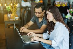 Man och kvinna som använder bärbara datorn i kafé Royaltyfri Bild