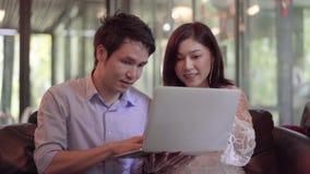 Man och kvinna som använder bärbara datorn i kafé arkivfilmer