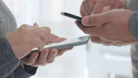 Man och kvinna som använder den smarta telefonen lager videofilmer