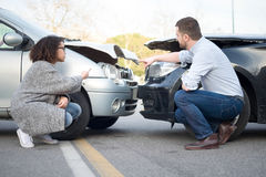 Man och kvinna som argumenterar efter en bilkrasch Arkivfoton